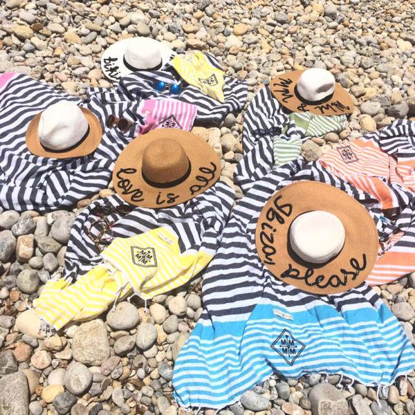 Foutas para presente exclusivo e personalizado expostas na praia de pedras com chapéu bordado por cima